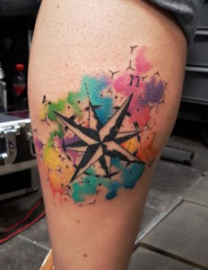 Abstrakter Kompass mit Aquarell-Elementen.